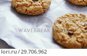 Купить «Freshly baked cookies on wax paper 4k», видеоролик № 29706962, снято 5 мая 2017 г. (c) Wavebreak Media / Фотобанк Лори