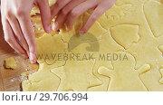 Купить «Woman removing gingerbread dough on wooden table 4k», видеоролик № 29706994, снято 5 мая 2017 г. (c) Wavebreak Media / Фотобанк Лори