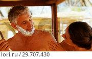 Купить «Smiling woman looking while man shaving his beard 4k», видеоролик № 29707430, снято 12 мая 2017 г. (c) Wavebreak Media / Фотобанк Лори