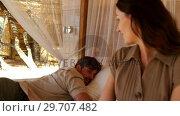 Smiling couple interacting in canopy bed 4k. Стоковое видео, агентство Wavebreak Media / Фотобанк Лори