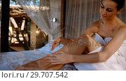 Woman applying lotion while sitting on canopy bed 4k. Стоковое видео, агентство Wavebreak Media / Фотобанк Лори