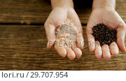 Купить «Hands holding sea salt and black pepper against wooden table 4k», видеоролик № 29707954, снято 5 июня 2017 г. (c) Wavebreak Media / Фотобанк Лори