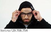 Купить «Man in hoodie wearing spectacles against white background 4k», видеоролик № 29708754, снято 16 мая 2017 г. (c) Wavebreak Media / Фотобанк Лори