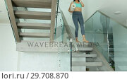 Купить «Woman with yoga mat walking down on stair case 4k», видеоролик № 29708870, снято 25 марта 2017 г. (c) Wavebreak Media / Фотобанк Лори