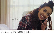 Купить «Woman laughing while talking on phone at home 4K 4k», видеоролик № 29709354, снято 31 мая 2017 г. (c) Wavebreak Media / Фотобанк Лори