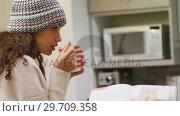 Купить «Woman in warm clothing having coffee 4K 4k», видеоролик № 29709358, снято 31 мая 2017 г. (c) Wavebreak Media / Фотобанк Лори
