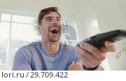Купить «Young man laughing while watching television at home 4K 4k», видеоролик № 29709422, снято 31 мая 2017 г. (c) Wavebreak Media / Фотобанк Лори