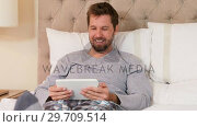 Купить «Smiling young man sitting on bed using his tablet in the bedroom 4K 4k», видеоролик № 29709514, снято 10 августа 2017 г. (c) Wavebreak Media / Фотобанк Лори