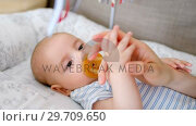 Купить «Cute little baby holding mom hand lying in baby crib 4k», видеоролик № 29709650, снято 8 ноября 2017 г. (c) Wavebreak Media / Фотобанк Лори