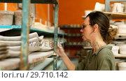 Купить «Female potter arranging craft product in shelf 4k», видеоролик № 29710142, снято 6 августа 2017 г. (c) Wavebreak Media / Фотобанк Лори