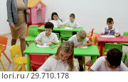 Купить «Cute schoolchildren drawing with teacher in classroom», видеоролик № 29710178, снято 18 декабря 2018 г. (c) Яков Филимонов / Фотобанк Лори