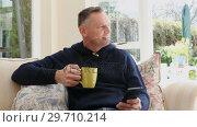 Купить «Man using mobile phone while having coffee in living room 4k», видеоролик № 29710214, снято 31 августа 2017 г. (c) Wavebreak Media / Фотобанк Лори