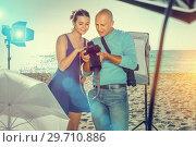 Купить «Photographer and model discussing picture on camera display duri», фото № 29710886, снято 5 октября 2018 г. (c) Яков Филимонов / Фотобанк Лори