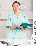 Купить «Girl doctor in medical coat holding clipboard with medical records», фото № 29710902, снято 1 мая 2018 г. (c) Яков Филимонов / Фотобанк Лори
