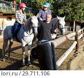 Купить «Positive mature couple with jockey learn to riding horse at farm», фото № 29711106, снято 4 июля 2018 г. (c) Яков Филимонов / Фотобанк Лори