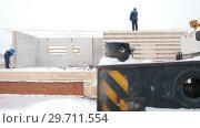 Купить «Construction site. People standing on the foundation of the building house», видеоролик № 29711554, снято 27 марта 2019 г. (c) Константин Шишкин / Фотобанк Лори