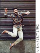Купить «Young bearded man jumping in urban background with open arms wearing casual clothes. », фото № 29712862, снято 7 ноября 2017 г. (c) Ingram Publishing / Фотобанк Лори