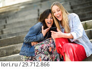 Купить «Two girls looking at some funny thing on their smart phone», фото № 29712866, снято 7 марта 2018 г. (c) Ingram Publishing / Фотобанк Лори