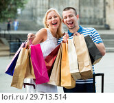 Купить «Young man and woman holding shopping paper bags», фото № 29713514, снято 23 января 2019 г. (c) Яков Филимонов / Фотобанк Лори