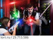 Купить «Excited guy laser tag player in bright beams», фото № 29713586, снято 25 апреля 2018 г. (c) Яков Филимонов / Фотобанк Лори