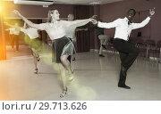 Купить «Young positive people dancing twist in pairs at dance hall together», фото № 29713626, снято 4 октября 2018 г. (c) Яков Филимонов / Фотобанк Лори