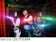 Купить «Young people playing laser tag in bright beams», фото № 29713694, снято 25 апреля 2018 г. (c) Яков Филимонов / Фотобанк Лори