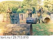Купить «Team of adult people playing paintball on battlefield outdoor, r», фото № 29713810, снято 22 сентября 2018 г. (c) Яков Филимонов / Фотобанк Лори