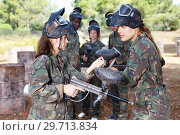Купить «Woman paintball coach in full gear instructing female player about marker gun before match», фото № 29713834, снято 11 августа 2018 г. (c) Яков Филимонов / Фотобанк Лори