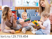 Cute babies playing musical toys with teacher and assistant. Early musical education in kindergarten. Стоковое фото, фотограф Оксана Кузьмина / Фотобанк Лори