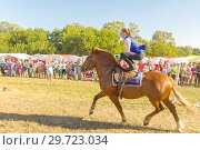 Купить «Russia, Samara, July, 2018: a Cossack girl rides a horse and performs tricks.», фото № 29723034, снято 29 июля 2018 г. (c) Акиньшин Владимир / Фотобанк Лори