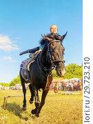 Купить «Russia, Samara, July, 2018: a Cossack girl rides a horse and performs tricks.», фото № 29723210, снято 29 июля 2018 г. (c) Акиньшин Владимир / Фотобанк Лори