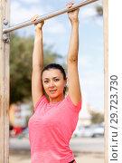 Купить «Woman training on outdoors fitness station», фото № 29723730, снято 26 июня 2018 г. (c) Яков Филимонов / Фотобанк Лори
