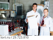 Купить «Two happy employees standing in packaging section on wine manufactory», фото № 29723810, снято 21 сентября 2016 г. (c) Яков Филимонов / Фотобанк Лори