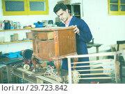 Craftsman inspecting nightstand before restoration. Стоковое фото, фотограф Яков Филимонов / Фотобанк Лори