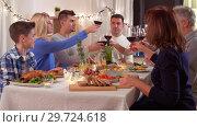 Купить «happy family having dinner party at home», видеоролик № 29724618, снято 7 января 2019 г. (c) Syda Productions / Фотобанк Лори