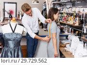 Купить «Tailor taking measurements of female client», фото № 29729562, снято 20 октября 2018 г. (c) Яков Филимонов / Фотобанк Лори