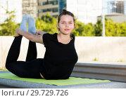 Купить «Young woman doing exercises outdoors», фото № 29729726, снято 5 июля 2017 г. (c) Яков Филимонов / Фотобанк Лори