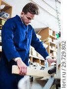 Купить «Man processing plank at workshop», фото № 29729802, снято 7 ноября 2016 г. (c) Яков Филимонов / Фотобанк Лори