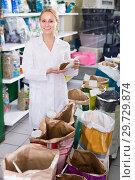 Купить «Young shop assistant offers to choose pet food», фото № 29729874, снято 6 декабря 2019 г. (c) Яков Филимонов / Фотобанк Лори