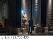 """Купить «Посетитель рассматривает деревянную скульптуру на выставке """"Христос в темнице"""". Центральный выставочный зал """"Манеж"""". Санкт-Петербург», эксклюзивное фото № 29730430, снято 16 января 2019 г. (c) Румянцева Наталия / Фотобанк Лори"""