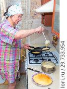 Купить «Mature woman bakes pancakes in the kitchen.», фото № 29733954, снято 12 февраля 2018 г. (c) Акиньшин Владимир / Фотобанк Лори