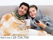 Купить «Couple together under blanket watching TV», фото № 29734794, снято 12 ноября 2019 г. (c) Яков Филимонов / Фотобанк Лори