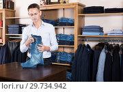 Купить «Handsome guy deciding on new trousers», фото № 29734942, снято 28 марта 2017 г. (c) Яков Филимонов / Фотобанк Лори
