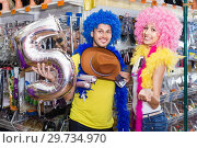 Купить «Family couple preparing for fest and choosing clown wigs», фото № 29734970, снято 11 апреля 2017 г. (c) Яков Филимонов / Фотобанк Лори