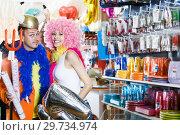 Купить «Cheerful couple trying on helmet with horns», фото № 29734974, снято 11 апреля 2017 г. (c) Яков Филимонов / Фотобанк Лори