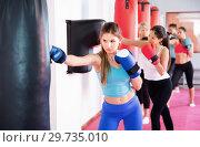 Купить «Sporty girl is boxing near punching bag in gym.», фото № 29735010, снято 8 октября 2017 г. (c) Яков Филимонов / Фотобанк Лори