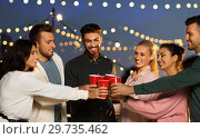 Купить «friends clinking party cups on rooftop at night», фото № 29735462, снято 2 сентября 2018 г. (c) Syda Productions / Фотобанк Лори