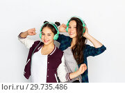 Купить «teenage girls in earphones listening to music», фото № 29735486, снято 19 декабря 2015 г. (c) Syda Productions / Фотобанк Лори