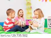 Купить «happy children playing with soft toys at home», фото № 29735502, снято 15 октября 2017 г. (c) Syda Productions / Фотобанк Лори