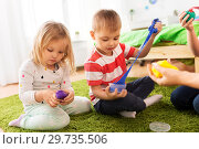 Купить «children with modelling clay or slimes at home», фото № 29735506, снято 15 октября 2017 г. (c) Syda Productions / Фотобанк Лори